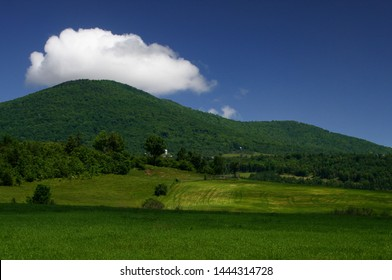 Summer in Vermont: Green Mountain and Field under White Clouds and Blue Sky, USA