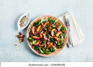 summer, very tasty salad with peaches, sweet onions and arugula with almonds on a table in a plate. simple healthy recipe