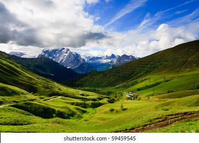 Summer view of Dolomites valley, under blue sky with clouds.