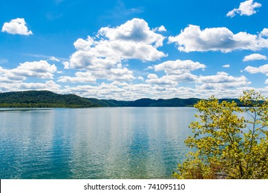 Summer view of local lake Cave Run with beautiful forest on lake hillside shore and dramatic cloudscape sky in Kentucky, USA