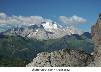 Summer view of Marmolada, the queen of Dolomites. Dolomiti peak Marmolada with a glacier. Green alpine meadows and forests and rock face of Marmolada.