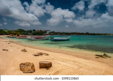 Summer view on the beach in Aruba with turquoise color Caribbean sea and few fishing boats anchored in the back.