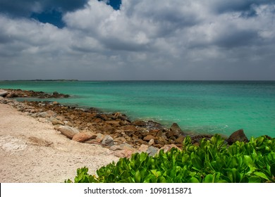Summer view on the beach in Aruba with turquoise color Caribbean sea.