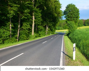 Summer view on empty automobile road with kilometer post among green fiels and forest trees. Empty car road. European car travel concept