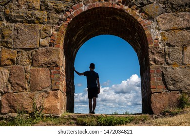 Summer view, silhouette of a young boy man leaning against an ancient old stone wall inside an arched gate looking at the blue sky. Varberg Fortress in Sweden.