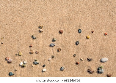 Summer view of small round pebbles on sunny beach, seen from above.