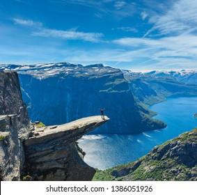 Die Sommeransicht von Trolltunga (berühmtes norvegisches Ziel der Trollzunge) und Ringedalsvatnet See in Odda, Roldal, Norwegen. Ein Mensch, der auf Felsen touristisch ist.