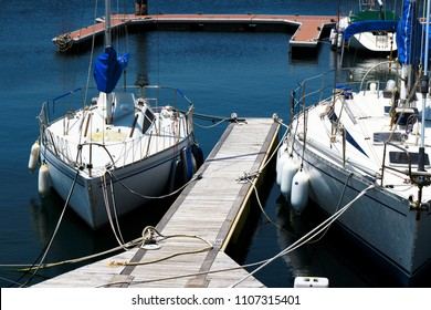 The summer view where the white yacht moored on the jetty of the yacht harbor shines on the surface of the water