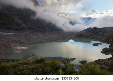 Summer views of the snowy mountains of the Caucasus. Formation and movement of clouds over mountains peaks.