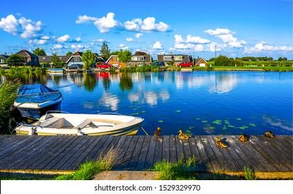Summer village river pier landscape. Ducks on village river pier. Village river pier ducks scene. Summer village river pier scene