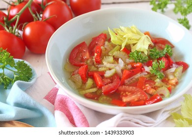Summer vitamin detox soup with celery, red bell pepper and tomatoes, parsley garnish