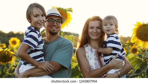 Summer walk in the field with sunflowers. A happy family is looking at the camera and smiling. Light flare, lens glare.