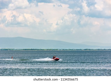 summer water sports on Zemplinska Sirava lake, Slovakia. Lovely place for vacation or weekend in summer. people have fun while water skiing and riding water scooter