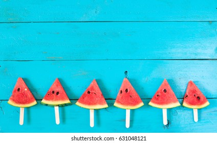 summer watermelon slice popsicles on a blue rustic wood background. copy space for designer
