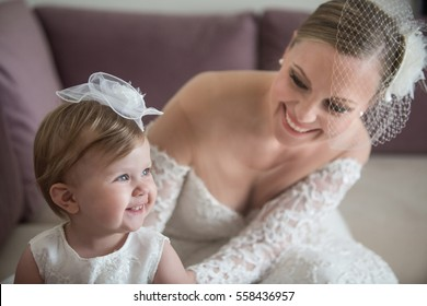 Summer wedding and baptism. Cute baby girl with her bride mother preparing for the ceremony.