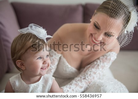 6fc0f4284ce Summer wedding and baptism. Cute baby girl with her bride mother preparing  for the ceremony