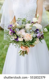 summer wedding bouquet in hands of the bride