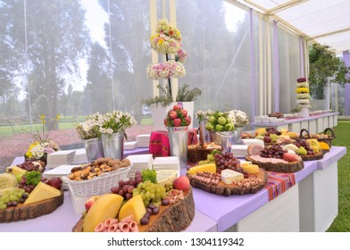 Summer wedding garden party with close up of a lavishly decorated fruit and cheese buffet table.