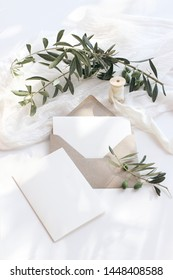 Summer wedding stationery mock-up scene. Blank greeting cards, envelope, olive branches and silk ribbon. White background with cotton table runner in sunlight, shadows. Flat lay, top view, vertical