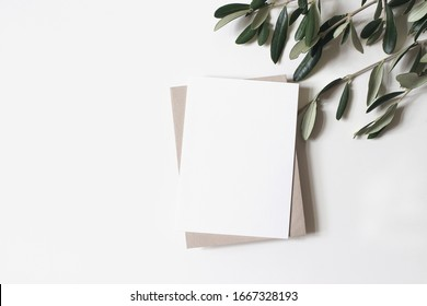 Summer wedding stationery mock-up scene. Blank vertical greeting card, craft paper envelope and olive branches isolated on white table background. Feminine Mediterranean flat lay, top view.