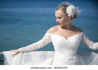 Summer wedding.Beautiful bride on the sea. Romantic beautiful bride in white dress posing on terrace with sea in background