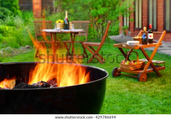 Summer Weekend BBQ Scene On The Backyard. Flaming Charcoal Grill Close Up. Outdoor Wooden Furniture  On The Blurred Background.