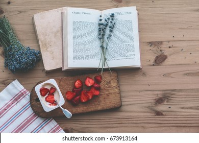 Summer weekend concept. Reading novel and relaxing. Opened book, lavender and yogurt with strawberry on old wooden table, top view.