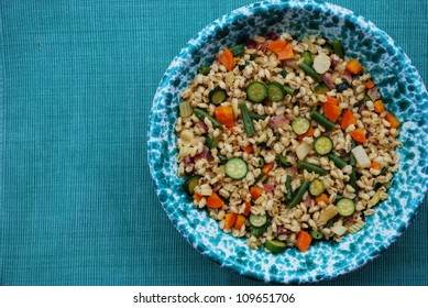 Summer whole barley salad with colorful vegetables in a green bowl