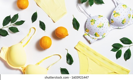 Summer woman cotton lingerie with lemons on white background, copy space. Flat lay, top view. Summer fashion concept. Nature friendly flat lay lingerie and natural elements on white background.