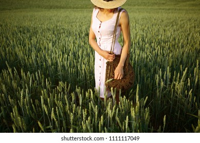Summer woman in green wheat field, nature, countryside rural style, straw hat linen pink dress and knitted bag, provences, outdoor