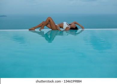 Summer. Woman model in fashion swimsuit lying on edge of infinity swimming pool with sea view. Girl in fashionable white bikini swimwear relaxing at luxury resort