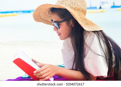 Summer woman relaxing in hipster beach hat and colorful sunglasses. Funky happy girl having fun during travel holidays vacation. Young trendy cool hipster woman reading a book and lying in the sand.
