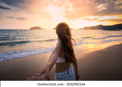 Summer woman vacations concept, Couple holding hands and walking on beach in sunset at Koh Mak, Thailand, Asia woman with white bikini and shorts jeans