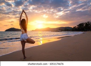 Summer woman vacations concept, Travel asia woman with white bikini and shorts jeans practicing yoga on sea beach in sunset at Koh Mak, Thailand