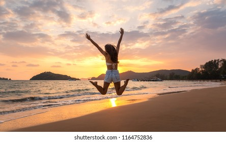 Summer woman vacations concept, Travel asian woman with white bikini and shorts jeans jumping on sea beach in sunset at Koh Mak, Thailand