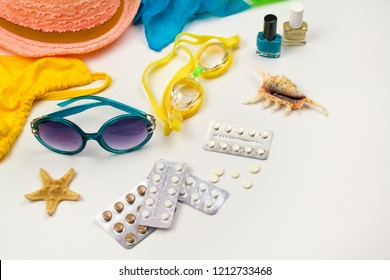 Summer womens beach accessories for your sea holiday and pill on white background. Concept of medication required in journey. Top view. Flat lay.