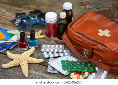 Summer women's beach accessories for your sea holiday and first aid kit on old wooden background. Concept of medication required in journey. Top view. Flat lay.
