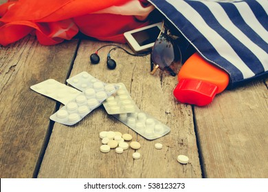 Summer women's beach accessories for your sea holiday and pill on old wooden background. Concept of medication required in journey. Toned image.