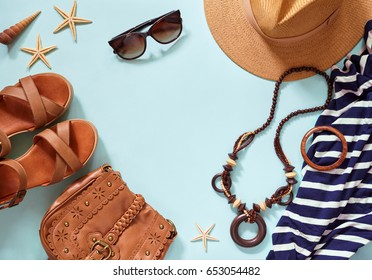 Summer women's beach accessories for your sea holiday: straw hat, bracelets, leather sandals, sun glasses, beads, leather bag and striped dress. Copy space for text. Flat lay on the blue background.