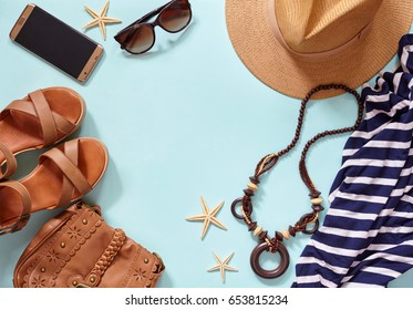 Summer women's beach modern trendy clothing accessories for sea travel vacation: hat, bracelets, sunglasses, beads, dress, golden smartphone. Flat lay blue background. Copy space fot text.