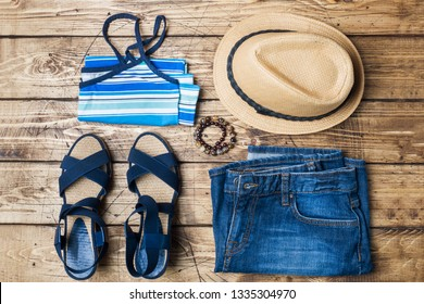 Summer women's clothes. Flat lay fashion photo. Blue jeans, t-shirt, sun hat, blue sandals on wooden background