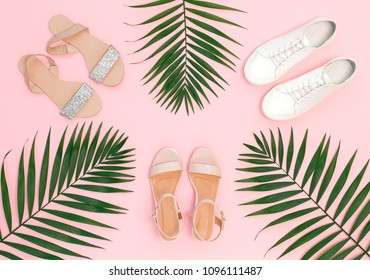 Summer women's shoes. Pink heeled sandal, silver glitter flat sandal, white lace up sneakers and tropical date palm leaves on pink background. Trendy beauty female background. Flat lay, top view.