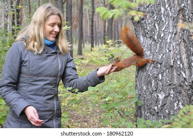 In the summer, the woods, the girl feeding a red squirrel.