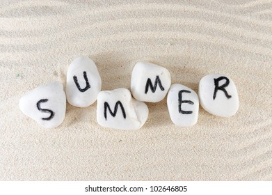 Summer word on group of stones with sand background
