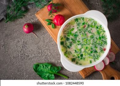 Summer yoghurt cold soup with radish, cucumber, and dill on wooden table. Okroshka.