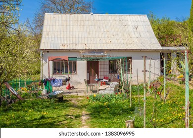 Summerhouse in the country. Small rural house with gardening equipment in the yard.  Nice cabana with flowers and gardening tools in the backyard.