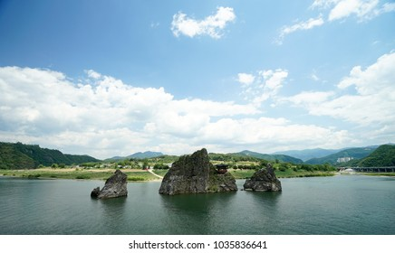 A summerhouse is on a rock on a river in Danyong, Korea. A boat is cruising around rocks with stream. Blue sky. Famous travel site.
