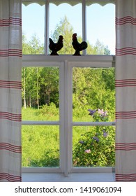 A summerhouse window with a green summer view.