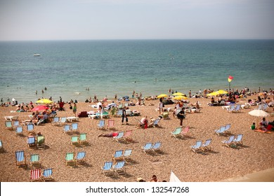 Summertime beach near ocean crowded with beach chairs and people on sunny day
