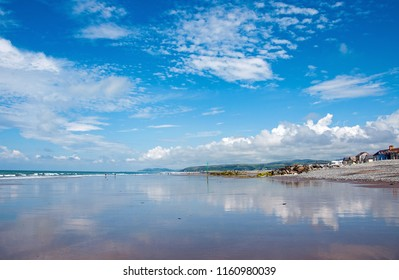 Summertime beach scene and reflections in the water along Cardigan bay, Wales.